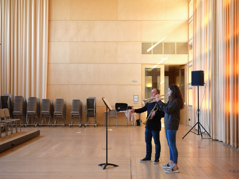 A student is performing to her teacher in a concert room of what appears to be a conservatoire.