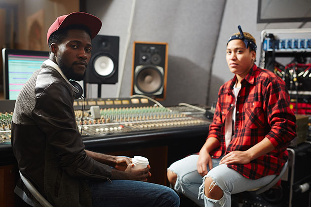 A photograph of two musicians sat in a studio next to a recording desk, they are both looking at the camera and one is holding a coffee.