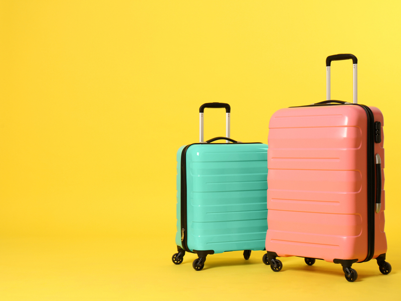 Photograph of two colourful suitcases against a bright yellow background.
