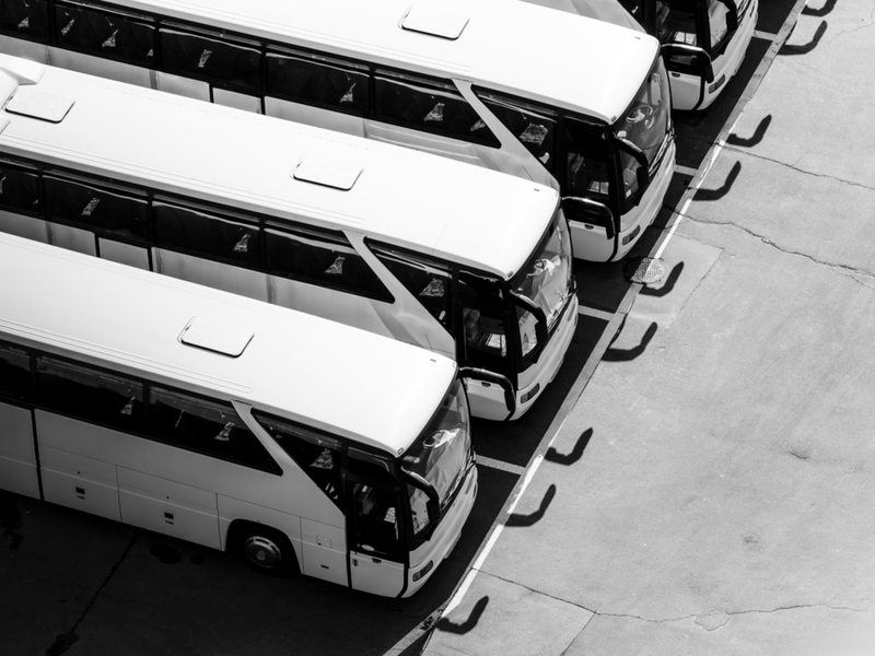 Black and white photo of a row of large your busses at a stand still.
