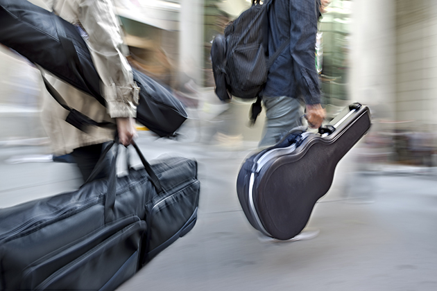 Photograph of two musicians, walking through a city and carrying instruments in travel cases.
