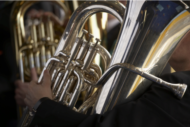 Photograph of a tuba being played, the musician is not visible apart from their hands and the background is black and shaded.
