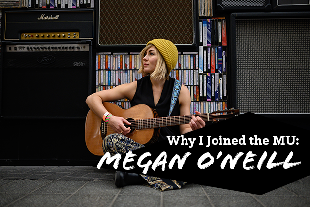 Photograph of Megan O'Neill sitting in front of an amplifier with a guitar
