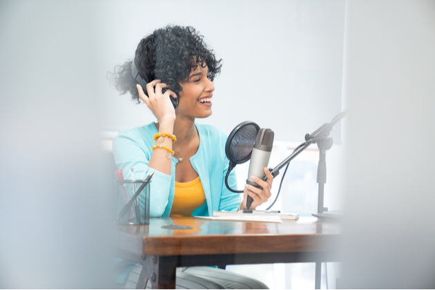 Photograph of a woman talking in a microphone, she appears to be recording something for a talk broadcast.