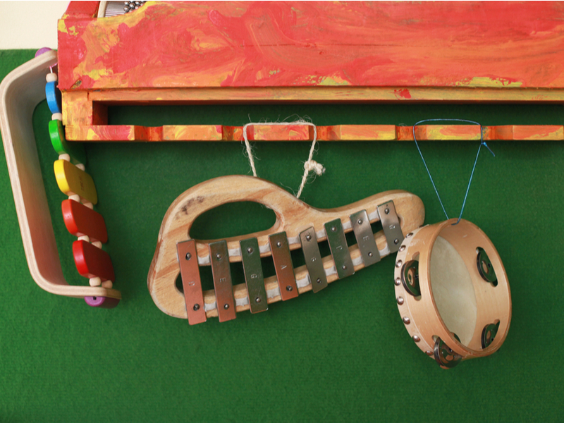 A selection of wooden, child-sized percussive instruments hanging from a peg board.