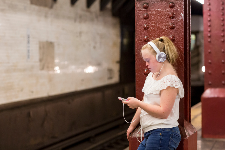 A young woman with Downs sydrome is leaning against a pillar at an underground station, listening to music.