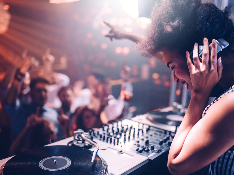 Photograph of a woman behind a DJ booth and mixing desk, looking out over the crowd in a busy club with a joyful expression on her face.