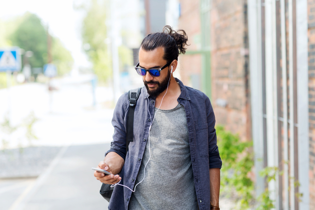 man with earphones and smartphone walking along city street and listening to podcast