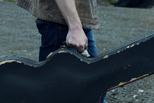 Photograph of a musician walking, whilst carrying a guitar in a hard case. We can only see the musicians arms and torso, the guitar case is well worn looking.