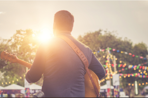 Photograph of a musician performing at an outdoor event. We can only seem them and the neck of their guitar from behind. The sun is setting and the evening lighting is turning on.