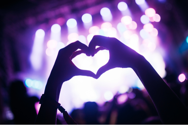 Photograph of an audience members hands, creating a heart shape with their fingers and held up in  silhouette against purple stage lights.