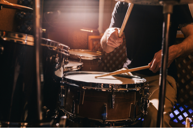 Photograph of a drum kit, a person sits behind the drum kit, we can just see their legs, arms and the drum sticks frozen in action.