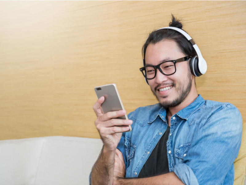 Photograph of a man sat listening to music through headphones which are connected to his mobile phone, he is smiling and happy looking.