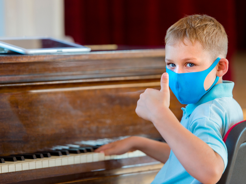 Young child wearing a mask is sat at a piano, turning round to face the camera he raises one thumb in a positive gesture.