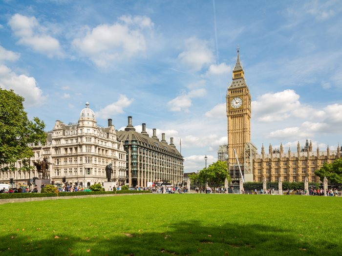 Photograph of Parliament square in the sunshine, the photograph looks across the square towards the houses of parliament and the grass is green.