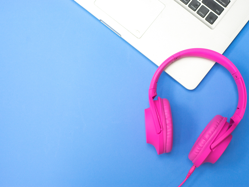 Photograph of bright pink earphones against a blue background, there is also the corner of an open silver laptop visible.