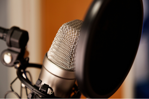 Photograph close up to a microphone set up in a recording studio.
