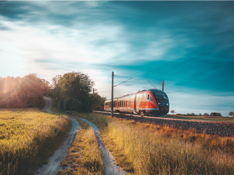 A German red train running in hazy dusky light through a field of yellowy green grass.