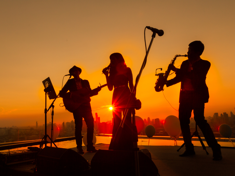 A band playing in silhouete outdoors against the sun setting in the background. They appear to be on a roof, there's a guitarist, a singer and a saxophone player.