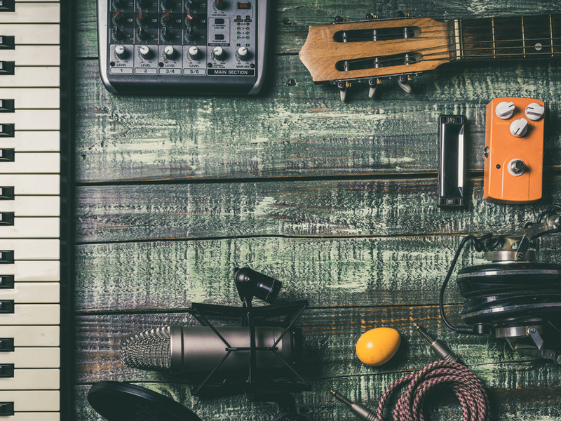 Photograph of various pieces of singer-songwriter equipment laid out, including microphone, keyboard, percussive egg and amp lead.