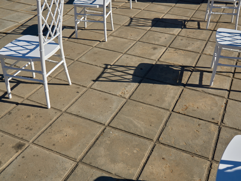 Photograph of white chairs in an outdoor setting, set out with socially distanced space around each one.