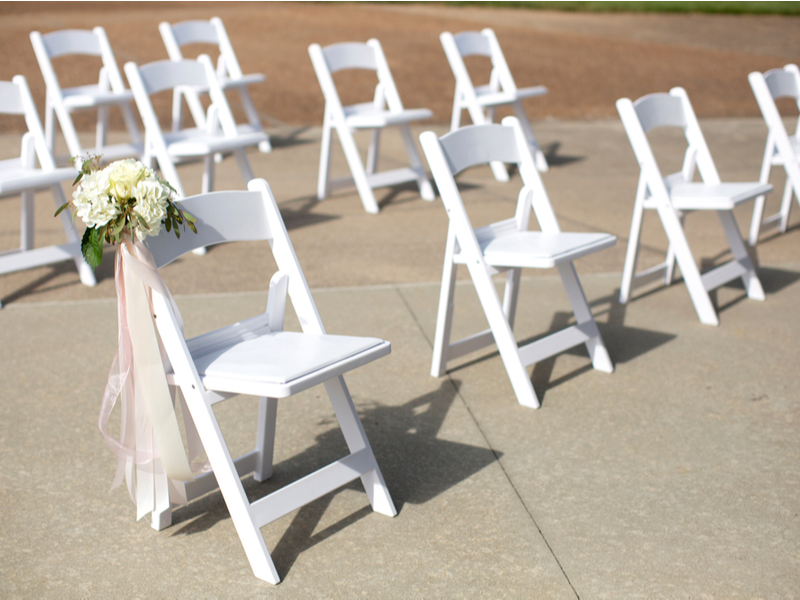 White painted chairs set out with socially distanced amount of space between them, outdoors.