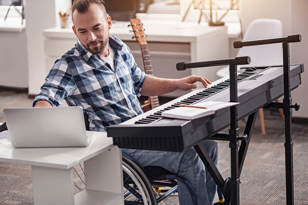 A white man in a wheelchair is indoors, performing in what appears to be his home on a keyboard, while leaning over to type something into his laptop.