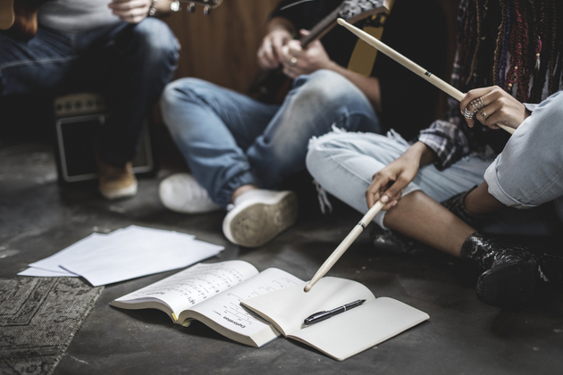 Photograph of a group of young students, rehearsing without their instruments out, but scores are laid out on the ground.